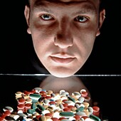 Male face with pills in foreground, Studio shot