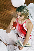 Young woman drinking fruit juice and reading a book