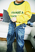 Child getting dressed, pulling his trousers up