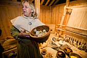 A woman serves a viking meal in a reconstructed longhouse at Qassiarsuk. the place were the first vikings with Erik the Red settled. South Greenland.