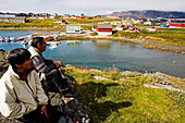 Two Inuit enjoy the view over Narsaq, South Greenland