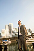 Young business man in front of modern office buildings, Neuer Zollhof, Architecture from Frank Gehry, Media Harbour Düsseldorf, state capital of NRW, North Rhine-Westphalia, Germany