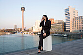 Young business woman talking on a mobile phone, in front of the city skyline, television tower, Zollhof, Media Harbour, architecture of Frank O.Gehry, Düsseldorf, state capital of NRW, North-Rhine-Westphalia, Germany