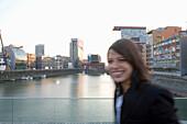 Woman walking past modern office buildings, Media Harbour, Düsseldorf, state capital of NRW, North-Rhine-Westphalia, Germany