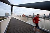 A person jogging over the footbridge, Media Harbour Düsseldorf, state capital of NRW, North-Rhine-Westphalia, Germany