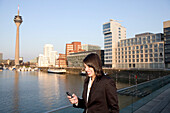 Young business woman writing an SMS, in front of the city skyline, Media Harbour, Düsseldorf with television tower and Zollhof, architecture of Frank O.Gehry, state capital of NRW, North-Rhine-Westphalia, Germany