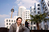 Young business in front of Neuer Zollhof, modern architecture from Frank Gehry, with television tower in the background, Media Harbour, Düsseldorf, state capital of NRW, North-Rhine-Westphalia, Germany