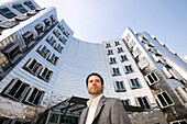 Young business man in front of Neuer Zollhof, modern architecture from Frank Gehry, Media Harbour, Düsseldorf, state capital of NRW, North-Rhine-Westphalia, Germany