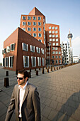 Young business man walking past Neuer Zollhof, modern architecture from Frank Gehry, Media Harbour, Düsseldorf, state capital of NRW, North-Rhine-Westphalia, Germany