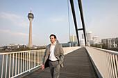 Man walking over footbridge, Media Harbour, Düsseldorf, state capital of NRW, North-Rhine-Westphalia, Germany