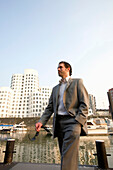 Young business man walking through Media Harbour, in front of modern architecture from Frank Gehry, office buildings, Düsseldorf, state capital of NRW, North-Rhine-Westphalia, Germany