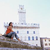 Touristin in Montepulciano, Toskana, Italien, Portrait, junge Frau, dunkelhaarig, orangenes Trägershirt, sitzt auf Stufen, Piazza Grande, Palazzo Comunale im Hintergrund, typisches Stadtbild, Rundfahrt, Tourismus, Sehenswürdigkeit, antik, Antike, mittelal