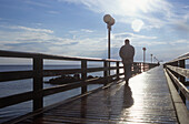 Man backlit on seabridge at Baltic sea, Dierhagen, Mecklenburg-Western Pomerania, Germany