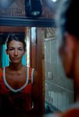 Woman looking at herself in mirror, bathroom, portrait