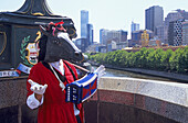 A costumed singer on Swanston Road with the Melbourne skyline and Yarra River in the back