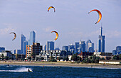 Kite surfing on St. Kilda beach in front of the skyline of downtown Melbourne, Victoria, Australia