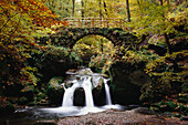Bridge and waterfall at Schiessentumpel in Mullerthal, Little Switzerland, Luxembourg