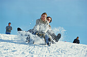 Couple having fun sledging down a hill in winter, Upper Bavaria, Germany