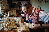 Wood Carver carving wood, Ortisei, Gardena, South Tyrol, Italy