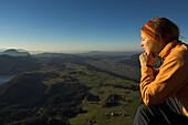 Woman with closed eyes sitting on top of mount Schoberstein, Lake Fuschl in background, Salzkammergut, Upper Austria, Austria