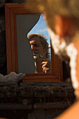 Reflection of a man shaving in a broken mirror, Madagascar, Africa