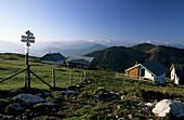 alpine huts at Benediktenwand with view to snow-covered range of Karwendel, range of Bavarian Alps, Upper Bavaria, Bavaria, Germany