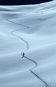 Backcountry skier in track in snow, Piz Laschadurella, Grisons, Switzerland