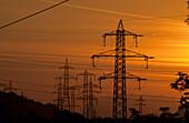 power lines against orange sky of sunrise, Kaiser range in background, valley of Inn, Tyrol