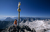 Woman next to summit cross on summit of Zugspitze, Wetterstein range, Upper Bavaria, Bavaria, Germany