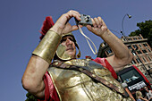 Man in Roman costume taking a photograph for tourist cameras near Colosseum, Rome, Italy