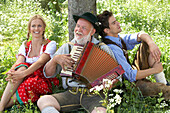 Couple listening to man playing melodeon