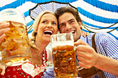 Couple clinking beer glasses in a beer tent