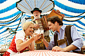 Couple clinking beer glasses in a beer tent, man playing melodeon in background