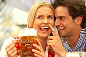 Couple enjoying a liter of beer in a beer tent
