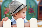 Boy (3-4 years) standing behind a fence