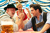 Two men arm wrestling in a beer tent