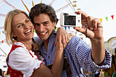 Mid adult couple photographing themselves with a digital camera