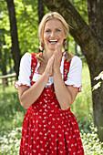 Mid adult woman wearing dirndl dress smiling at camera