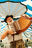 Man wearing bavarian costume playing melodeon
