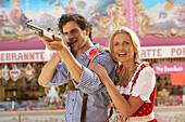 Couple at shooting gallery, Oktoberfest, Munich, Bavaria, Germany