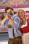 Man aiming at camera, Oktoberfest, Munich, Bavaria, Germany