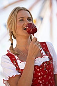 Woman wearing dirndl dress eating candied apple