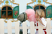 Children (3-5 years) eating pink cotton candy