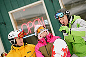 Three skiers in front of T-Bar pub, Castle Mountain ski resort, Alberta, Canada
