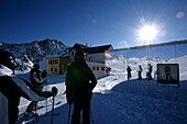 Skiers with reflection on Facade at alpine hut Bella Vista, Schnalstal, South Tyrol, Italy
