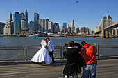 Smiling for a wedding photo in front of the East River and Brooklyn Bridge, Manhattan