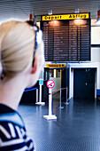 Junge Frau blickt auf Informationstafel am Flughafen, Luxemburg