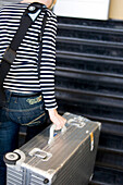 Woman with aluminium suitcase on staircase, airport, Luxemburg