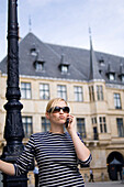 Young blond on the cell in front of Grand Ducal Palace, Luxembourg