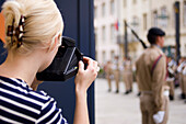 Young woman photographing changing of the guard at Grand Ducal Palace, Luxembourg, Luxembourg
